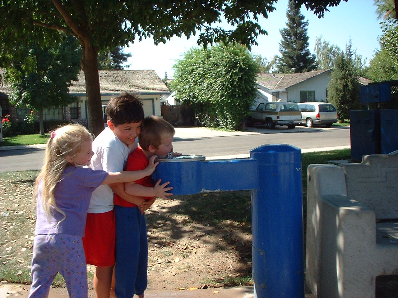 three kids at drinking fountain